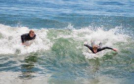 Two surfers riding waves in Reid State Park in Georgetown, Maine.