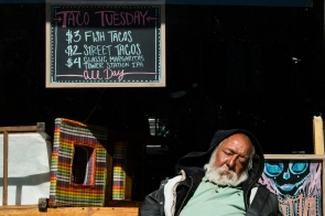 Anthony Ortiz, one of many houseless individuals in Flagstaff, sleeps on a bench in front of La Santisima.